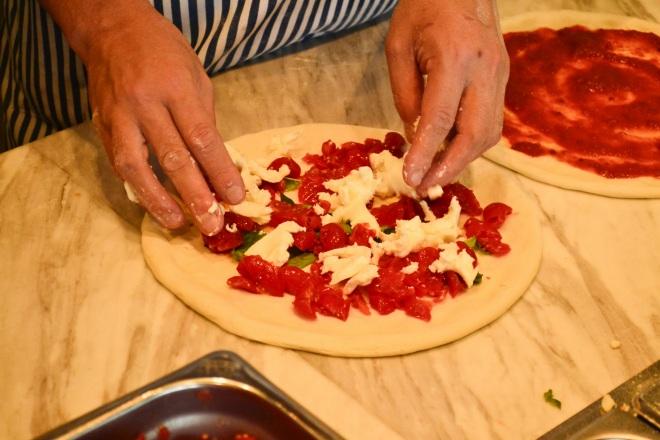 チーズや真っ赤なプチトマトを本場ナポリ風にトッピングする