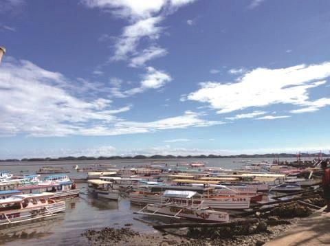 青空の下、埠頭にはアイランドホッピング用のモーター付き小舟がずらり