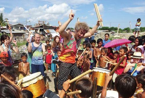 和太鼓を体験する貧困層のこどもたちと和太鼓バンドのメンバー=セブ日本人会提供
