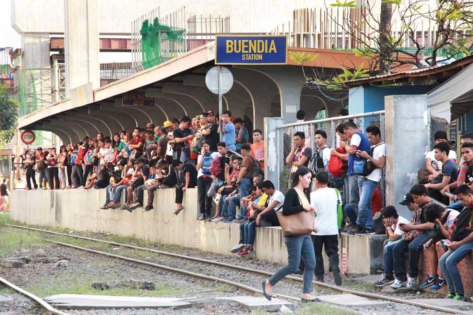 過密状態の現在の通勤列車(マカティ市のブエンディア駅で列車の到着を待つ人たち)