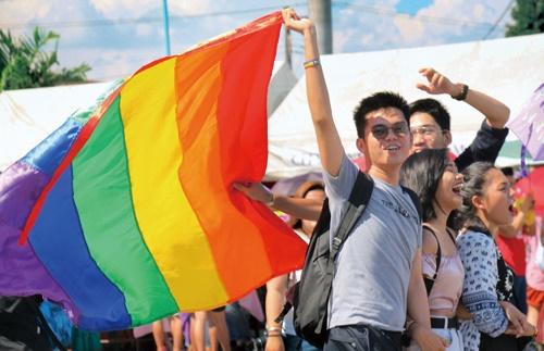 LGBT社会運動を象徴する虹色の旗を掲げ歩く参加者=6月24日午後3時ごろ、首都圏マリキナ市で冨田すみれ子撮影