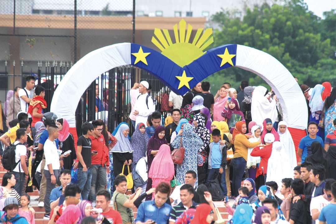 フィリピン国旗をデザインしたハート形のゲート前に集うムスリムの人たち。ラマダン明けの集団礼拝会場で(2016年7月6日)。ドゥテルテ大統領はこの日、「イスラム教徒とフィリピン人が手を携えて、平和で安定した永続的な社会を実現しよう」との声明を発表した。