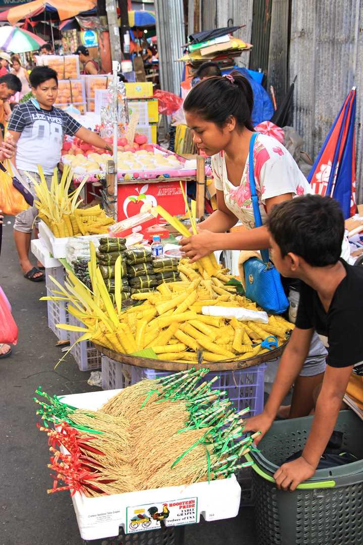 バナナの皮で手巻きした「スーマン」を売る女性。餅菓子はこのようなかごに盛られて売られていることが多い