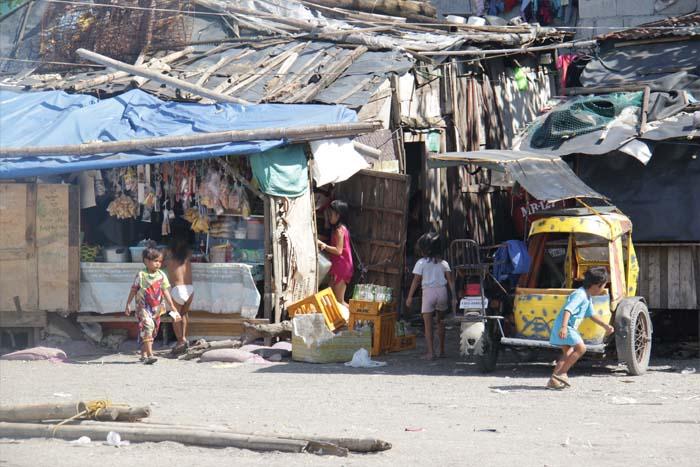 今にも崩れそうな商店。店主の姿はなく子供たちの姿が目立つ。 Poorly built houses for families with lots of kids. Pinagtagpi-tagping mga bahay para sa napakaraming Pamilya na may malaking bilang na anak