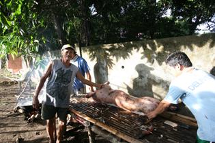 主が誇らしげに豚を横手にポーズを決める The landlord proudly poses with a pig