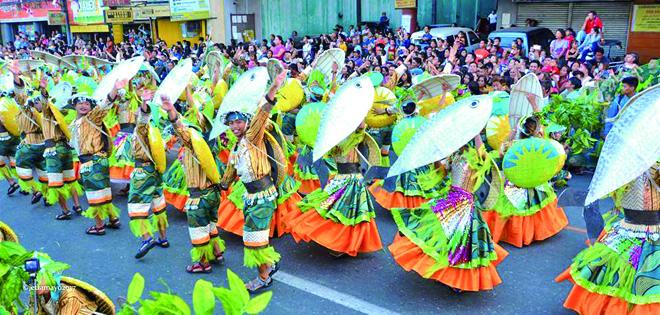 美しく着飾り、バグスの模型を持って踊る人々 (写真:Bangus Festival Execom)
